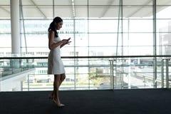 Vista laterale della donna di affari che utilizza telefono cellulare nell'ufficio e camminando su un passaggio pedonale del tappe immagini stock