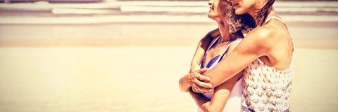 Vista laterale della donna felice che abbraccia sua madre alla spiaggia immagine stock