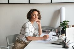 Vista laterale della donna impressionante che si siede dalla tavola Fotografia Stock