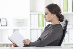 Vista laterale della donna nella lettura grigia nell'ufficio immagini stock
