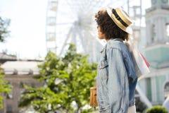Vista laterale della donna riccia alla moda con i sacchetti della spesa fotografia stock libera da diritti