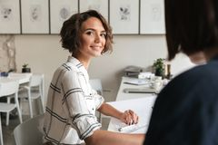 Vista laterale della donna riccia sorridente di affari che si siede dalla tavola Fotografia Stock