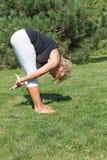 Vista laterale della donna senior flessibile che allunga esercizio Fotografia Stock