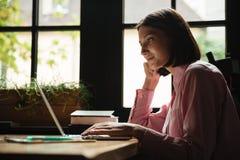Vista laterale della donna sorridente che si siede dalla tavola in caffè Fotografia Stock