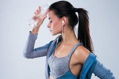 Vista laterale della donna stanca di sport con gli occhi chiusi che tengono bottiglia di acqua sulla sua fronte sopra fondo grigi Fotografie Stock