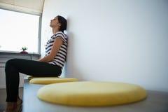 Vista laterale della donna sul sedile in ufficio Immagine Stock