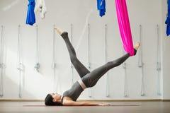 Vista laterale della giovane donna che fa yoga antigravità facendo uso dell'amaca Immagine Stock