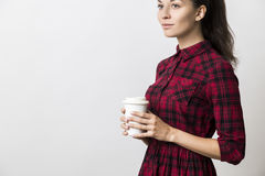 Vista laterale della giovane donna premurosa in vestito rosso con la tazza di caffè Fotografia Stock