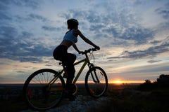 Vista laterale della giovane signora che cicla in montagne con un paesaggio di sera fotografia stock