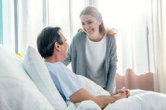Vista laterale della moglie sorridente che visita marito anziano fotografie stock libere da diritti