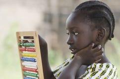 Vista laterale della ragazza africana della scuola che impara sull'abaco immagini stock libere da diritti