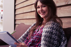 Vista laterale della ragazza sorridente che esamina la macchina fotografica mentre sedendosi sopra Fotografia Stock