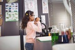 Vista laterale della scolara elementare che esamina tramite il microscopio il laboratorio Fotografia Stock