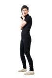 Vista laterale della spia femminile prudente in vestiti neri con la pistola che guarda dietro Fotografie Stock Libere da Diritti