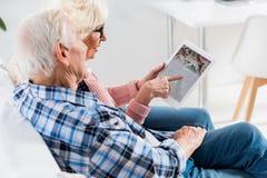 vista laterale delle coppie senior facendo uso della compressa digitale con foursquare immagine stock