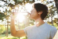 Vista laterale delle cuffie d'uso di un giovane sportivo asiatico fotografia stock libera da diritti