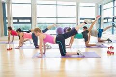 Vista laterale delle donne che allungano sulle stuoie alla classe di yoga Fotografia Stock