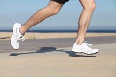 Vista laterale delle gambe di un uomo che corrono sul calcestruzzo di un lungonmare fotografia stock