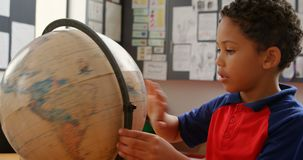 Vista laterale dello scolaro afroamericano che studia globo allo scrittorio in aula alla scuola 4k video d archivio