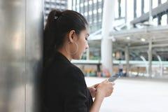 Vista laterale dello Smart Phone mobile della giovane tenuta asiatica attraente della donna sulla via della città Concetto social fotografia stock libera da diritti