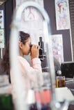 Vista laterale dello studente elementare che esamina tramite il microscopio il laboratorio Fotografia Stock
