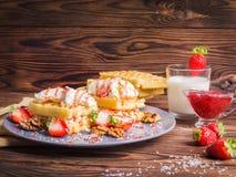 Vista laterale Dessert delle cialde accanto ad un bicchiere di latte su una tavola del servizio Fotografia Stock