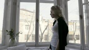 Vista laterale di bella bionda esile a casa dalla finestra azione Ragazza con il cardigan nero sulle sue spalle video d archivio