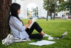 Vista laterale di bella studentessa asiatica, studiante nel parco, o Fotografia Stock Libera da Diritti
