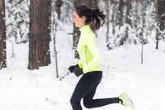 Vista laterale di funzionamento sportivo della giovane donna nell'allenamento di addestramento della via di inverno di mattina Immagini Stock