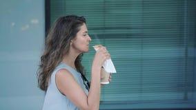 Vista laterale di giovane caffè mangiante e bevente giusto della donna dei capelli mentre camminando stock footage