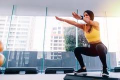 Vista laterale di giovane donna asiatica attraente di forma fisica in abiti sportivi che fanno edificio occupato profondo alla pa fotografia stock