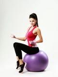 Vista laterale di giovane donna di sport che si siede sul fitball con i dumbells Fotografia Stock
