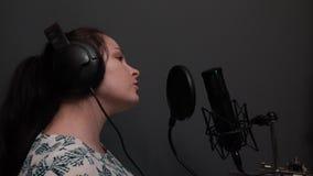 Vista laterale di giovane ragazza attraente con la canzone lunga di canto dei capelli allo studio vocale Registrazione di musica  archivi video