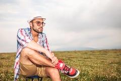 Vista laterale di giovane uomo casuale che si siede sulla sedia Fotografia Stock Libera da Diritti