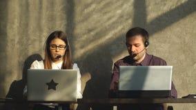 Vista laterale di giovane uomo d'affari bello e di bella donna di affari in cuffie avricolari facendo uso dei computer portatili  archivi video