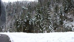 Vista laterale di guida di veicoli attraverso le montagne nell'inverno stock footage