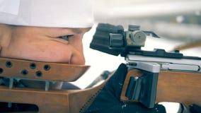 Vista laterale di un atleta di signora che tende dall'arma di biathlon stock footage
