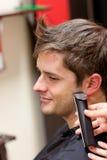 Vista laterale di un barbiere che rade un cliente maschio fotografie stock libere da diritti