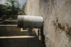 Vista laterale di un tubo non finito di drenaggio che attacca fuori una parete grigia fotografia stock