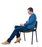 Vista laterale di un uomo che si siede su una sedia per studiare con un computer portatile Fotografia Stock