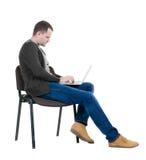 Vista laterale di un uomo che si siede su una sedia per studiare con un computer portatile Fotografie Stock Libere da Diritti