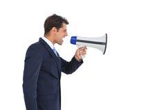 Vista laterale di un uomo d'affari che grida sul suo megafono Fotografia Stock