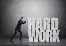 Vista laterale di un uomo d'affari che spinge grande calcestruzzo 3d & x27; work& duro x27; parole Fotografie Stock