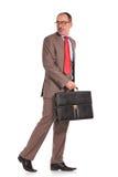 Vista laterale di un uomo d'affari di camminata che guarda indietro immagini stock