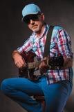 Vista laterale di un uomo maturo che gioca una chitarra elettrica Fotografia Stock