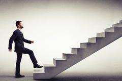 Vista laterale di un uomo in un'usura convenzionale che scala le scale concrete Immagine Stock