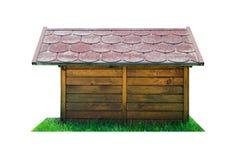 Vista laterale di una capanna di legno del cane con un tetto rosso, stante sull'erba verde Isolato su una priorità bassa bianca c immagine stock