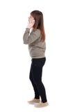 Vista laterale di una donna che cammina con il telefono cellulare Immagine Stock