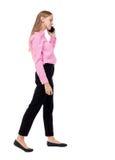 Vista laterale di una donna che cammina con un telefono cellulare ofgi posteriore di vista Immagini Stock