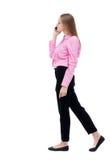 Vista laterale di una donna che cammina con un telefono cellulare ofgi posteriore di vista Fotografie Stock